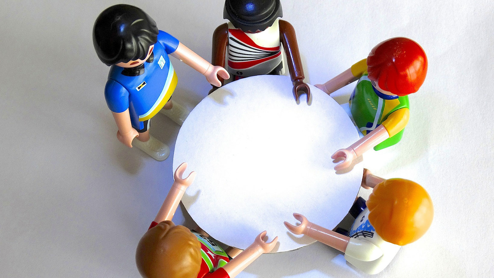 Mehrere Personen aus Playmobil an einem Tisch