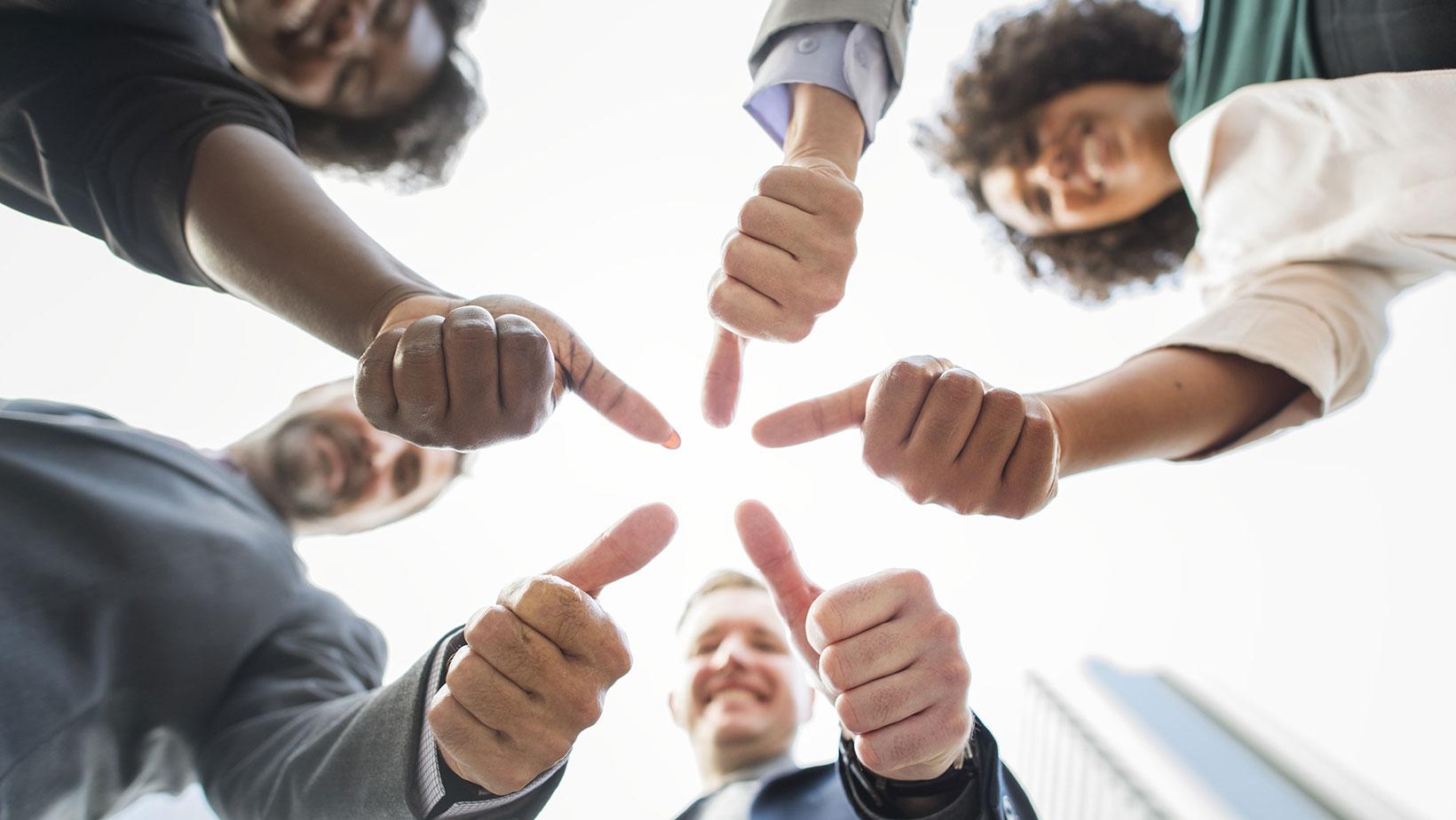 Symbolbild Nebenjob: Eine Gruppe Menschen steht im Kreis und recht die Daumen nach oben.